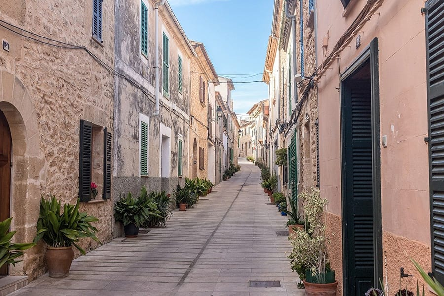 narrow paved street with old stone houses either side